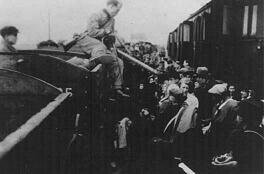 Jews from the Lodz ghetto are forced to transfer to a narrow-gauge railroad at Kolo during deportation to the Chelmno extermination camp. Kolo, Poland, probably 1942. - US Holocaust Memorial Museum