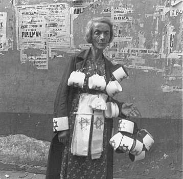An emaciated woman sells the compulsory Star of David armbands for Jews. In the background are concert posters; almost all are destroyed. Warsaw ghetto, Poland, September 19, 1941. - Guenther Schwarberg; US Holocaust Memorial Museum