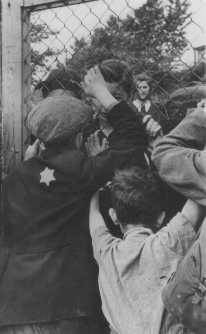 Jewish children say goodbye to parents through the fence of the Central Prison, the assembly point for deportations. Lodz ghetto, Poland, between 1942 and 1943. - Beit Lohamei Haghettaot