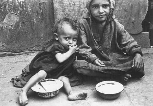 Children eating in the ghetto streets. Warsaw, Poland, between 1940 and 1943. - US Holocaust Memorial Museum