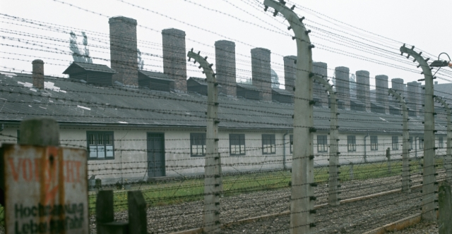 Fences surround the concentration camp at Auschwitz. An estimated 1,000,000 to 2,500,000 people were exterminated at the camp. A row of chimneys tops the crematorium, were bodies were burned. - History.com