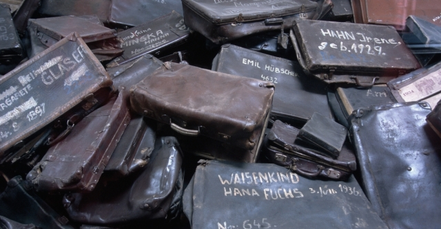 Battered suitcases sit in a pile in a room at Auschwitz. The cases, most inscribed with each owner's name, were taken from prisoners upon their arrival at the camps. - History.com